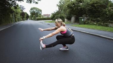 Fitness Girl Fitness girl does pistol squat exercise on the street