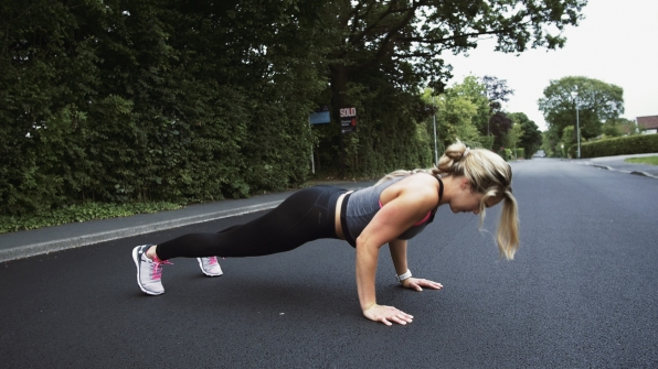 Fitness girl does press-ups on the street